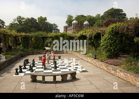 Children playing chess on a giant board in the walled garden Burton Agnes Hall East Yorkshire UK - Stock Photo