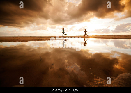 Two children running along the beach on a cloudy day, Reflection, Segeltorpstrandet, Halmstadt, Skane, Sweden - Stock Photo