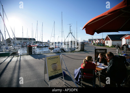 Three people sitting in a cafe at the harbour, Torekov, Skane, Sweden - Stock Photo