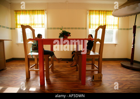 Two women sitting on enlarged furniture, chairs, like little Tom Thumb, Astrid Lindgren World, Vimmerby, Smaland, - Stock Photo