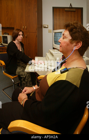 Test equipment checks for the possibility of tumors on an adult's auditory nerve at an Orange, CA speech & hearing - Stock Photo