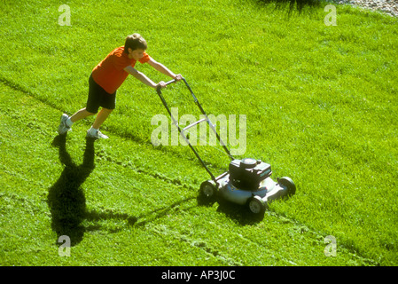Teenager doing chores by mowing lawn with power mower - Stock Photo