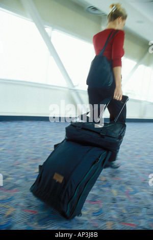 Pulling Baggage through Airport - Stock Photo