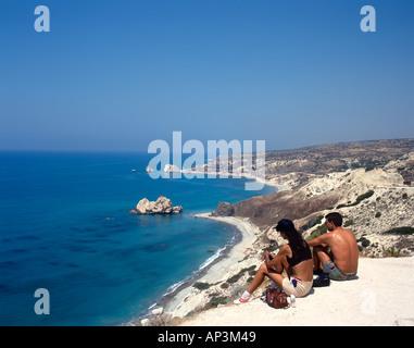 Couple sitting at a lookout over Aphrodite's Rock (or Petra tou Romiou), near Pissouri, West Coast, Cyprus - Stock Photo