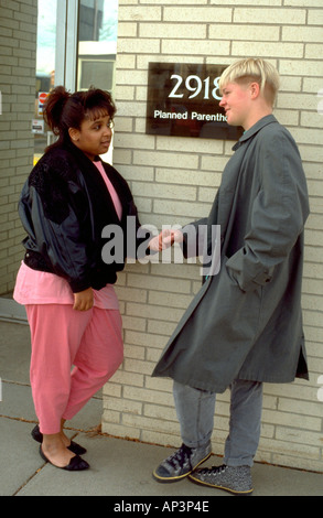Black and white teen couple age 16 outside of family planning clinic. Minneapolis Minnesota MN USA - Stock Photo
