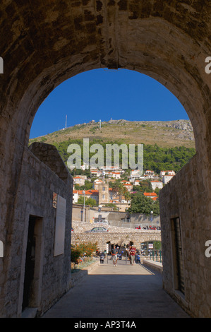 View of the hills and new houses through the city wall arch at Vrata od Buze Dubrovnik Dalmatia Croatia - Stock Photo