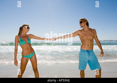 Man pulling woman by hand - Stock Photo