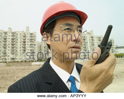 Man on building site with walkie talkie - Stock Photo
