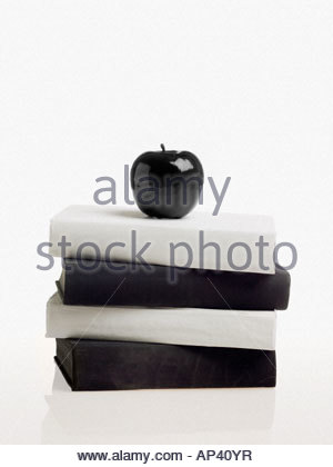 Black apple on top of pile of books - Stock Photo