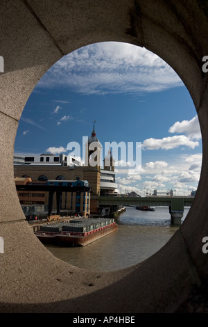 View down the River Thames towards Cannon Street train station through port hole on Southwark Bridge - Stock Photo