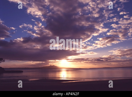 The sun rises from behind Rangitoto Island, off the coast of Auckland, New Zealand - Stock Photo