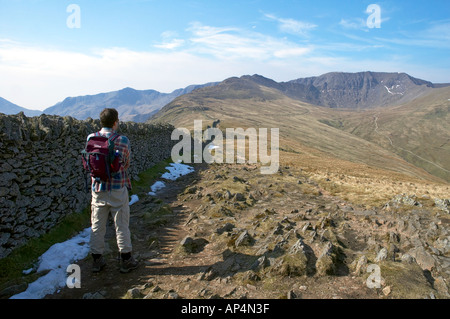 A male walker pausing as he looks towards the summit of Helvellyn in the English Lake District - Stock Photo