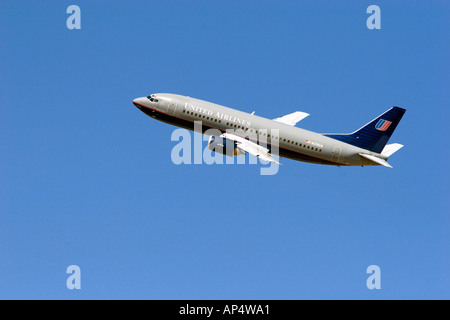 United Airlines Boeing 737 climbs out into a blue sky  - Stock Photo