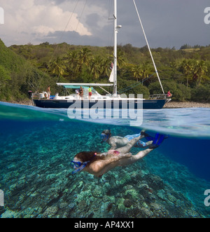 Snorkelers underwater and sailboat above, in Honolua Bay, Maui, Hawaii. All are model released. - Stock Photo