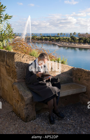 Palma Mallorca Spain A woman reads by the wall of Le Seu Cathedral in Palma - Stock Photo