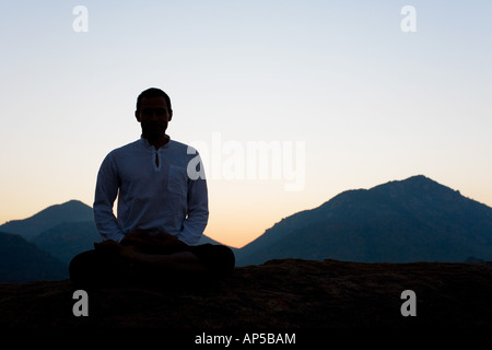 Silhouette of a man meditating on an Indian mountain top. India - Stock Photo