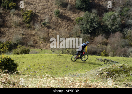 Off road cyclist decending a hill near Meldon reservoir in Dartmoor National Park Devon England - Stock Photo
