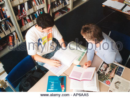 Tutor helping student fill in application form for higher education careers office sixth form college UK - Stock Photo