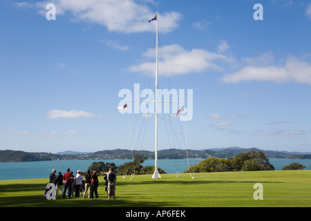 Tourists by historic naval flagstaff where treaty was signed at Waitangi National Reserve in Treaty House grounds. - Stock Photo