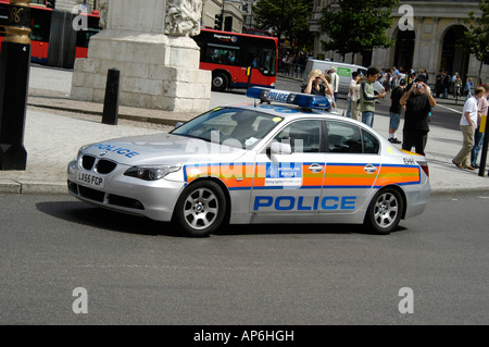 silver bmw police car driving through the city of london, england - Stock Photo