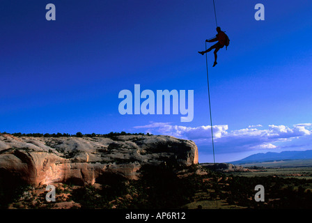 Man abseiling on rope in landscape of in Fisher Towers, Colorado River Waterway Near Castle Valley, Moab, Utah, - Stock Photo
