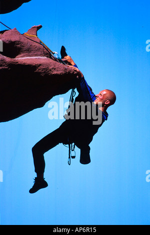 Rock climber on overhang in Fisher Towers, Colorado River Waterway near Castle Valley in Moab, Utah, USA - Stock Photo