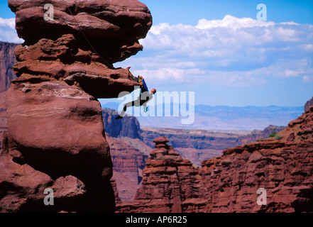 Rock climber hanging from cliff face in Fisher Towers, Colorado River Waterway Near Castle Valley in Moab, Utah, - Stock Photo