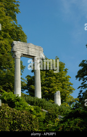 The remains of a Roman building standing isolated and mysterious in the woods Space for text in the sky - Stock Photo