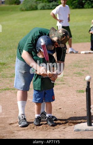 5 to 7 year old Children get their first experience playing baseball from a T - Stock Photo