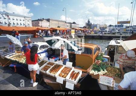 People buying and selling fresh fish off back of boats in market place at South Harbor in Helsinki - Stock Photo