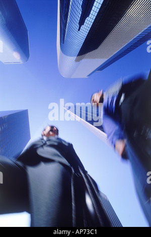 Business partners moving through Los Angeles skyscrapers - Stock Photo