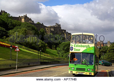 A green tourist bus on the Mound with the Castle behind, Edinburgh SCOTLAND - Stock Photo