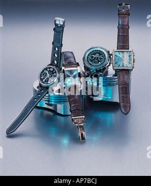 Four wristwatches on car piston heads - Stock Photo