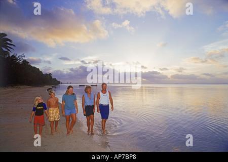 Family on Aitutaki Island lagoon at sunset in South Pacific - Stock Photo