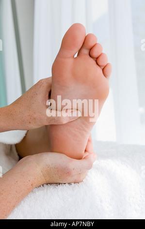 Woman having her foot massaged - Stock Photo