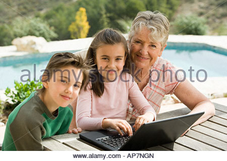 Woman and grandchildren with laptop - Stock Photo