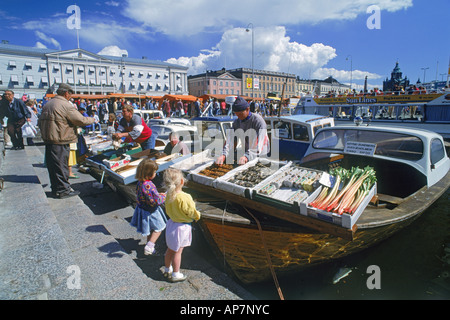 Children and adults buying and selling fresh fish and vegetables off back of boats in market place at South Harbor - Stock Photo
