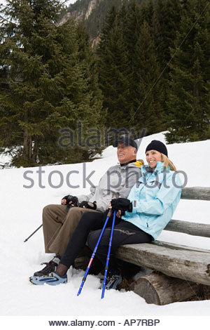 Couple sitting on bench in snow - Stock Photo