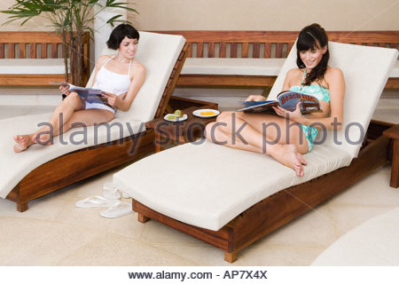 Women on lounge chairs with magazines - Stock Photo