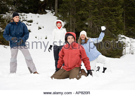 Friends having a snowball fight - Stock Photo