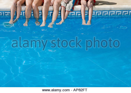 Family with feet in swimming pool - Stock Photo