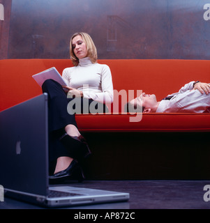 Businesswoman reading documents with businessman sleeping on a couch - Stock Photo