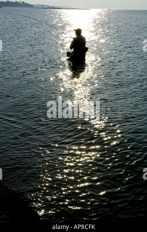 Silhouette of lone fisherman wading in water at Compo Beach, Westport, Connecticut at sunrise. - Stock Photo