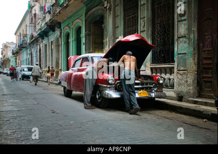 Classic American Car sits parked outside old buildings in Havana (Cuba) with two men repairing the Engine. - Stock Photo