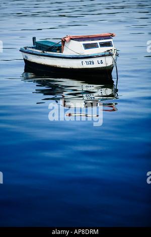 Small Fishing Boat sat in Havana Harbour opposite Castillo de los Tres Reyes del Morro. - Stock Photo