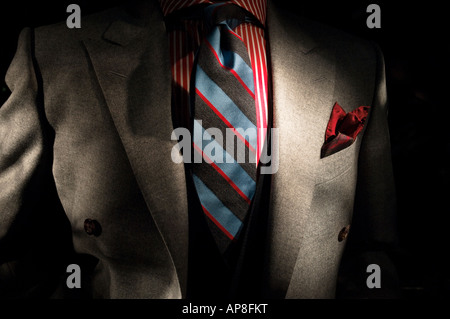 Double breasted gray suit jacket, burgundy and white striped shirt, burgundy and blue tie with a burgundy ascot - Stock Photo