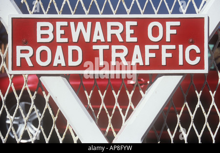 Bold metal sign painted white on scarlet red on gate with red car driving past and stating Beware of Road traffic - Stock Photo