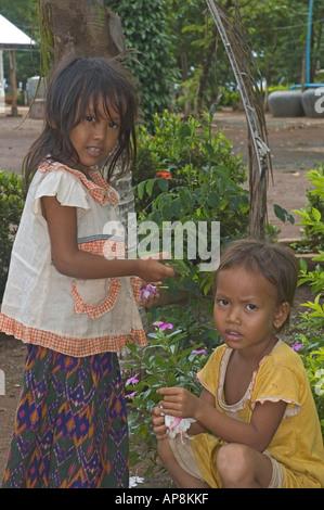 Cambodia Kampong Cham Wat Hanchey Buddhist Temple young girls in garden - Stock Photo