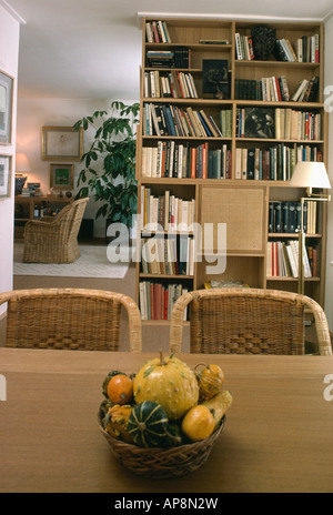 Bowl of gourds on table in neutral sixties dining room with wall of bookshelves - Stock Photo