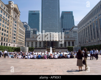 Office workers on their lunch break enjoying the spring sunshine Canary Wharf Docklands London England - Stock Photo